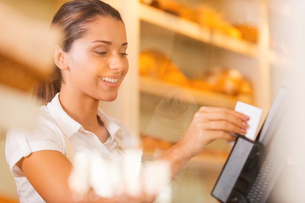 Woman accepting credit card payment at point of sale terminal